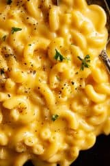 A close up of ultra creamy and cheese mac and cheese sprinkled with black pepper and a little parsley.