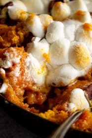 A close up of a scoop of sweet potato casserole take out and you can see the melty marshmallows.