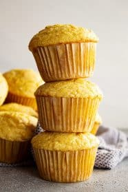 Three cornbread muffins stacked on top of each other with more muffins in the background.