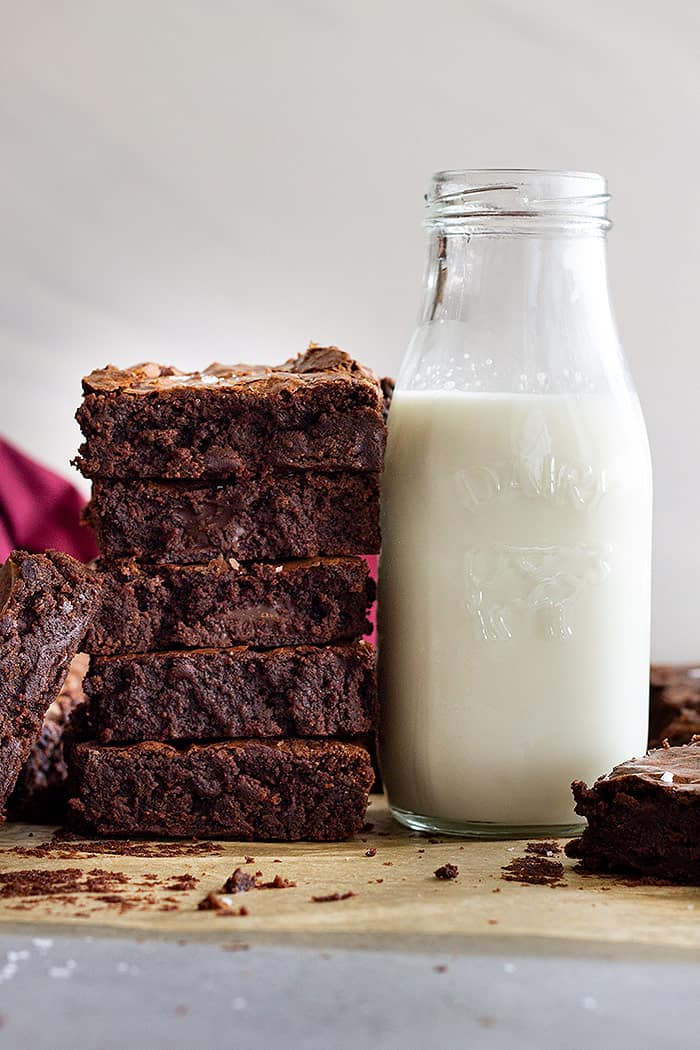 A tall stack of fudgy brownies next to a tall glass of cold milk.