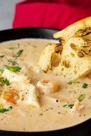 Close up of seafood bisque in a bowl with a piece of crusty bread dipping into it.