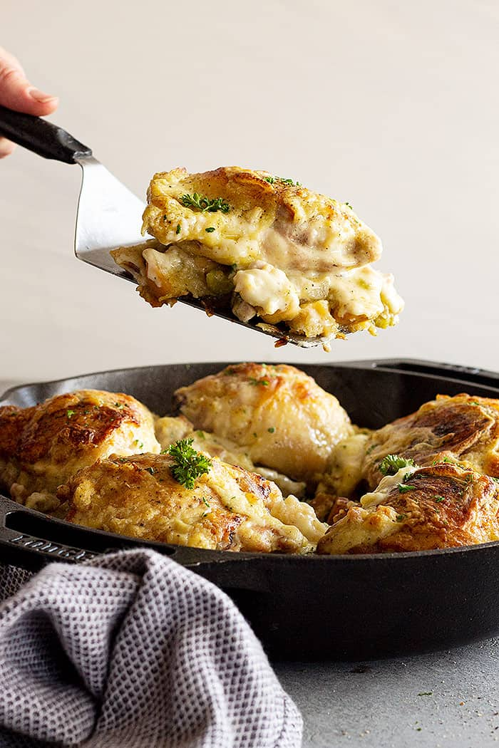 Lifting a portion of the casserole out of the pan ready to serve onto a plate.