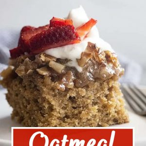 A piece of oatmeal cake on a white plate topped with fresh whipped cream and strawberries.