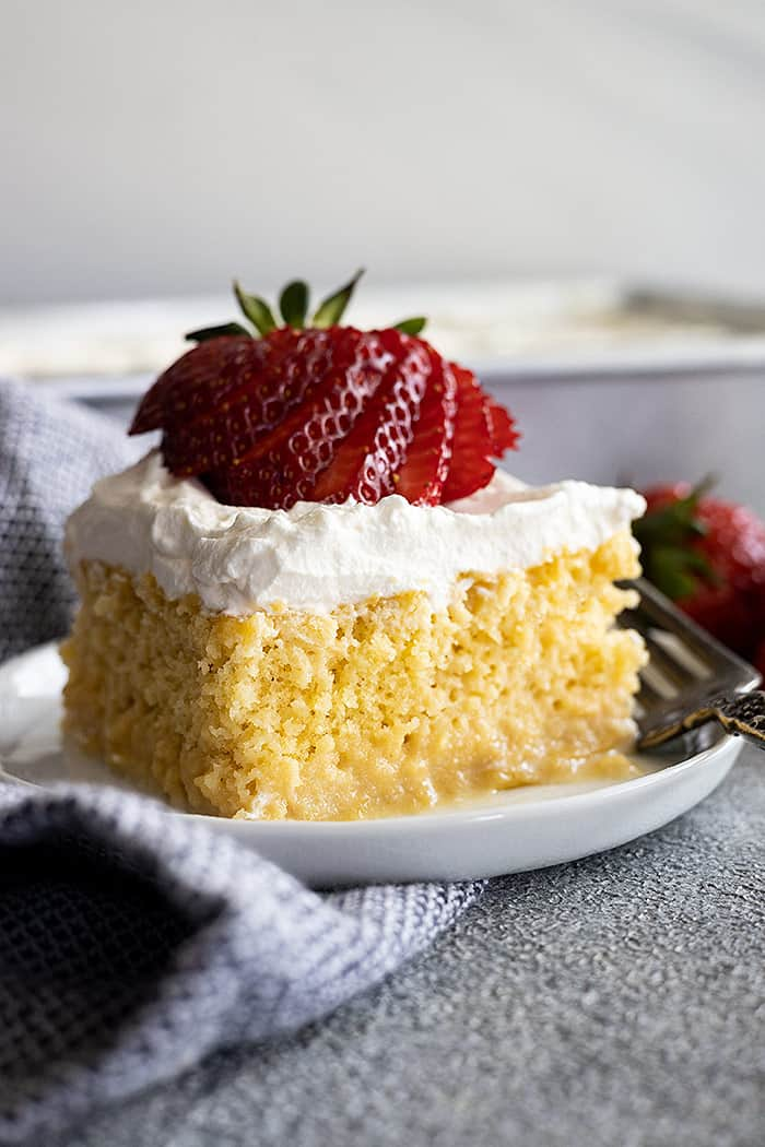 A piece of tres leches cake on a small plate topped with a fanned out strawberry.