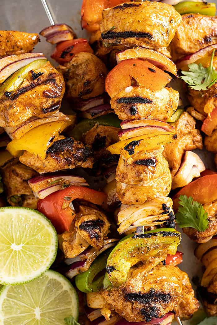 Close up picture of grilled chicken kebabs. Garnished with lime slices and cilantro.