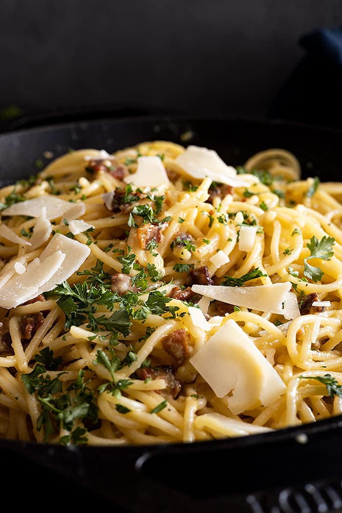 Close up of carbonara garnished with pieces of shaved parmesan and parsley.