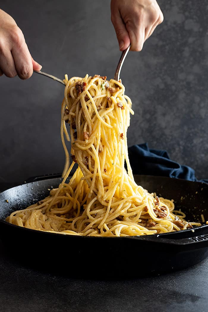 Two forks pulling up a generous portion of spaghetti carbonara ready to serve.