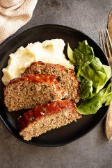 Overhead view of slices of tender meatloaf over mashed potatoes with a spinach salad.