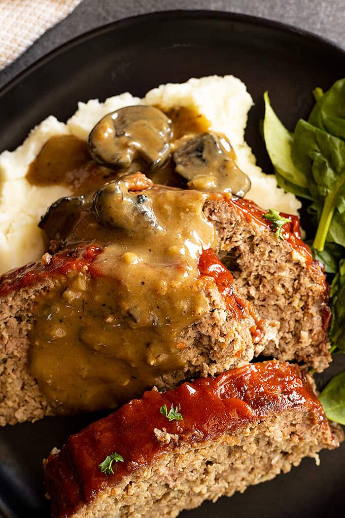 Easy mushroom gravy spooned over 3 slices of Old Fashioned Meatloaf and mashed potatoes.